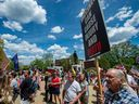 Rally goers hold signs protesting vaccines at an anti-vaccine rally in Concord, N.H., on May 15.